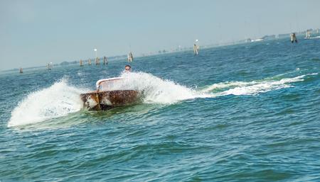 venice: Speedboat splashing in the blue Venice lagoon