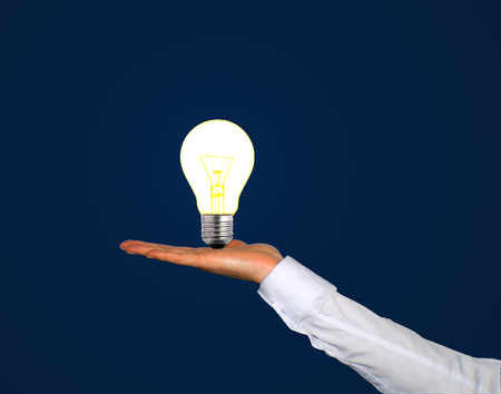 Switched on lightbulb in a human hand