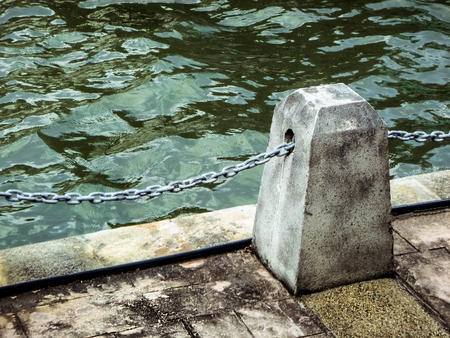 Piece of city waterfront with stone block and metal chain on background of rippled water.