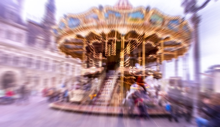 Spinning carousel in radial blur in front of Hotel de Ville in Paris, France Stock Photo