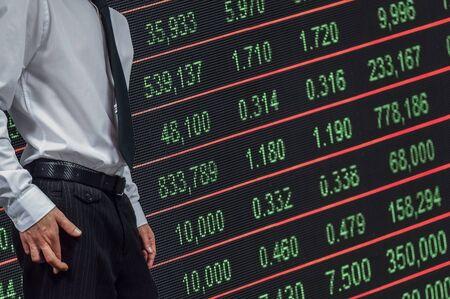 Business man crossing his fingers on top of stock market number Banco de Imagens