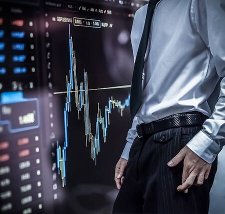 Business man crossing his fingers on top of stock market numbers and graph