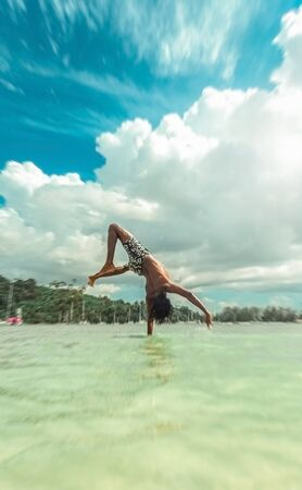 Young man doing acrobatics in the water in tropical location
