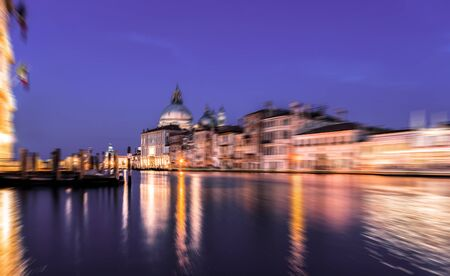 View of Grand Canal and Basilica della Salute at night with boat night trails with radial blur Banco de Imagens