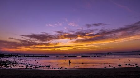 Man meditating in the sea in front of sunset