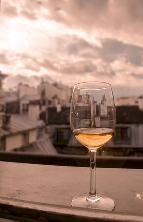 Glass of white wine on window sill with view of Paris roof tops