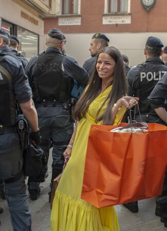 Rich woman with Hermes bag being photographed among police force during a manifestation
