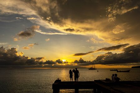 Perfect family holiday: silhouette of parents and child by the sea at sunset