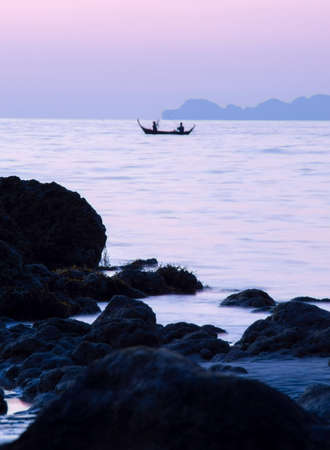 Two fisherman fishing in front of rocky beach at purple dusk