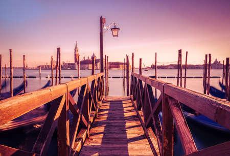 Pier with gondolas in long exposure in venice at sunset Archivio Fotografico