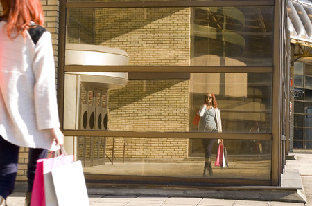 paperbag: Young cheerful woman holding shopping bags at the mall