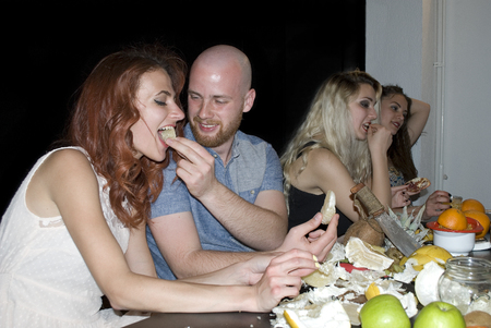 Group of young attractive people eating tropical fruits