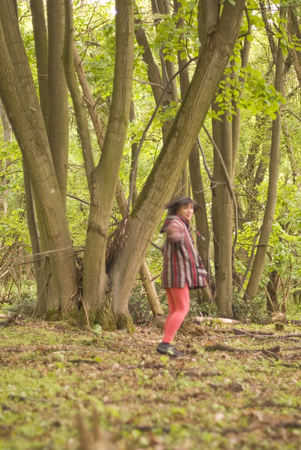thru: Woman wearing hoodie walking thru green forest - motion blur