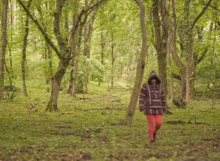 thru: Woman wearing hoodie walking thru green forest