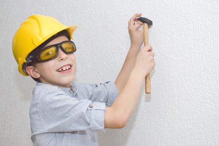 Boy with helmet and hammer on stepladder