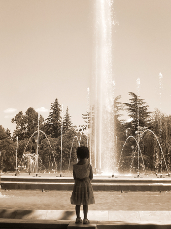 Cute little girl looking at fountain - sepia toning Stock Photo