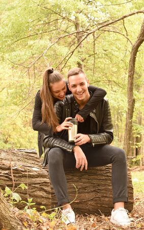 Happy Young couple sitting in autumn park Stock Photo