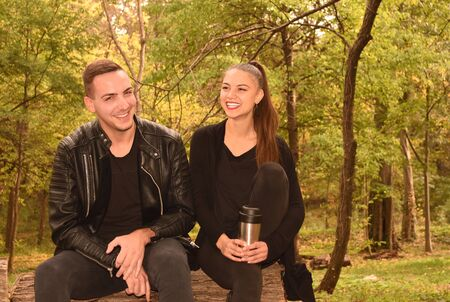 Young smiled couple sitting in autumn park