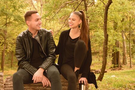 Young couple sitting in autumn park