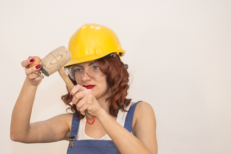Young Attractive Woman Smashing Eggs With Hammer - Funny Food Concept