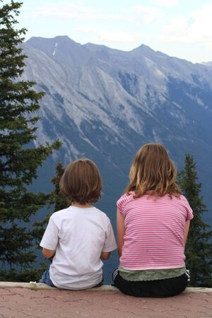 A young brother and sister enjoying a lofty mountain view 写真素材