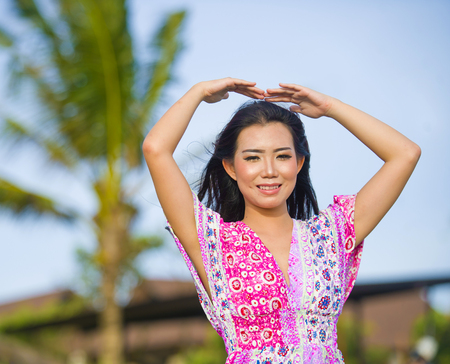 young happy beautiful Asian Chinese tourist woman doing love sign with arms above her head posing and laughing at beach tropical resort on holidays trip enjoying in travel destination concept Stock Photo