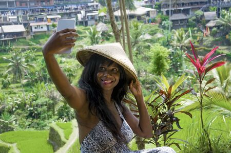 young attractive happy afro american black woman tourist taking selfie portrait photo with mobile phone camera while exploring rice fields forest and jungle in Bali wearing traditional Asian hat