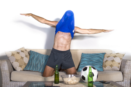 young attractive man happy and excited watching football match on TV celebrating victory goal crazy with team jersey over his head in fan and supporter lifestyle concept Stock Photo