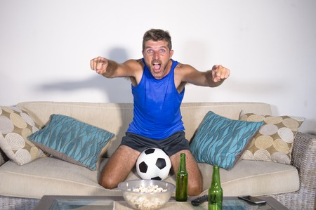 young attractive man happy and excited watching football match on TV celebrating victory goal crazy and spastic with beer popcorn and soccer ball in fan and supporter lifestyle concept