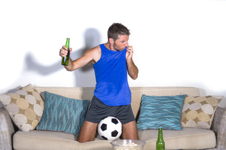 young attractive man happy and excited watching football match on TV celebrating victory goal crazy kissing team shirld jersey in fan and supporter lifestyle concept Stock Photo