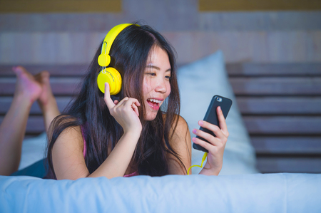 young sweet and happy Asian Chinese 20s woman listening to music song with headphones headset and mobile phone lying in bed relaxed late at night in media technology and lifestyle concept 版權商用圖片