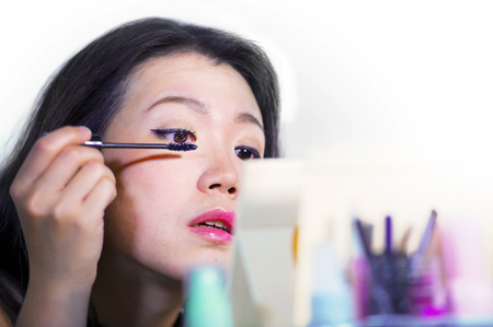 close up portrait of young beautiful and sweet Asian Chinese woman 20s or 30s applying mascara on her eye in make up session looking at the mirror using beauty products in female lifestyle concept Stock Photo