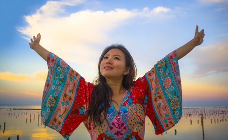 young happy and beautiful Korean woman in traditional Asian dress at sunrise sea landscape looking away with arms opened feeling free enjoying the beach breeze in holidays trip concept Stock Photo