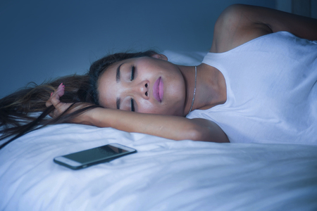 portrait of young beautiful Asian Thai woman 20s or 30s sleeping and resting lying on bed at her apartment bedroom with mobile phone next to her in internet social media app addiction concept