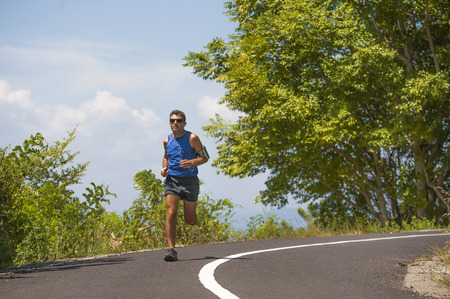 young attractive sport runner man training in asphalt road running workout a sunny Summer morning surrounded by trees and vegetation in healthy lifestyle body care and fitness concept