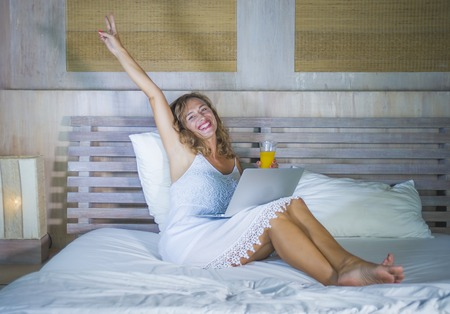 young attractive and beautiful happy Caucasian woman 30s lying in bed at home using internet working on computer laptop smiling excited and cheerful at her bedroom in morning lifestyle concept Stock Photo