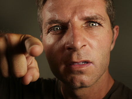 close up portrait of young angry and upset man pointing with finger as if scolding and blaming you in rage feeling rageful showing intense mad and displeased face expression isolated  Stock Photo