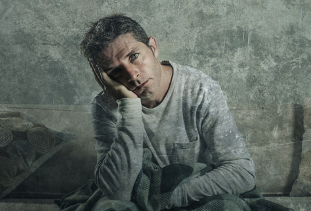 young sad and desperate man at home sitting at living sofa couch suffering depression and stress feeling miserable in frustration concept and lifestyle concept in harsh grunge background Stock fotó