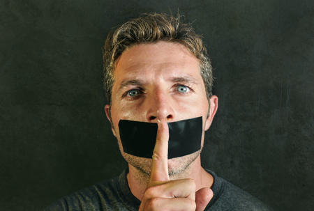 young man with mouth and lips sealed covered with adhesive tape in censorship coerced freedom of speech and forced silence and secrecy concept isolated on dark grunge background Stock Photo