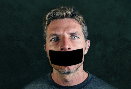 young man with mouth and lips sealed covered with adhesive tape in censorship coerced freedom of speech and forced silence and secrecy concept isolated on dark grunge background Stockfoto