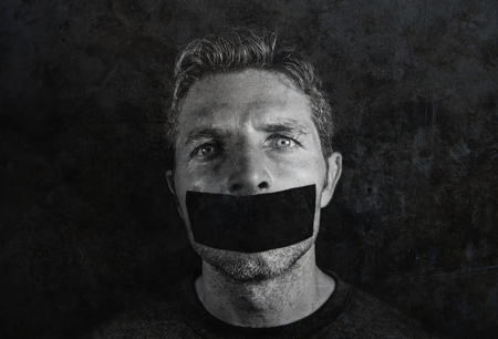 young man with mouth and lips sealed covered with adhesive tape in censorship coerced freedom of speech and forced silence and secrecy concept isolated on grunge black and white Stockfoto