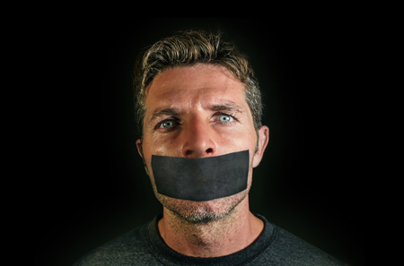 young man with mouth and lips sealed covered with adhesive tape in censorship coerced freedom of speech and forced silence and secrecy concept isolated on dark black background