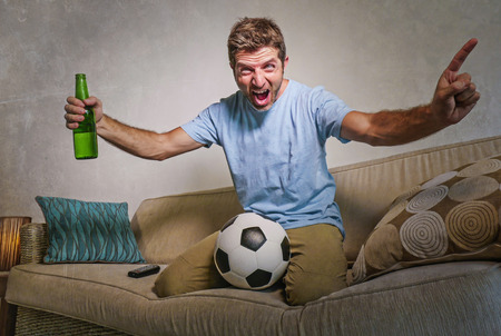 young happy excited and crazy football fan man holding soccer ball celebrating team scoring goal and victory watching game on television screaming spastic drinking beer bottle Фото со стока