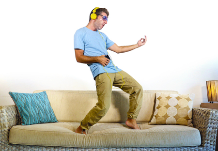 young happy and excited man jumping on sofa couch listening to music with mobile phone and headphones playing air guitar crazy having fun at home living room in audio fan lifestyle concept
