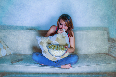 young beautiful and scared woman watching horror suspense movie and eating popcorn at home sofa couch late night in fear expression covering mouth with pillow grunge background