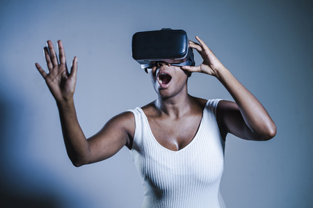 young attractive curious black afro american woman wearing VR 3d vision goggles enjoying amazing experience playing and having fun in virtual reality video game on isolated background