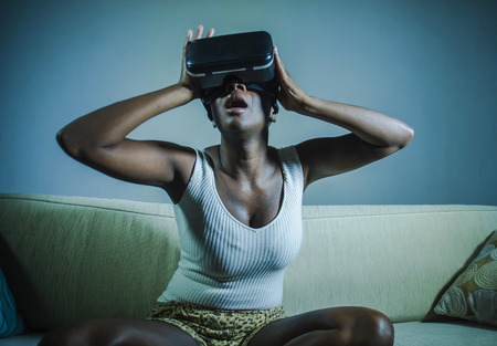young attractive black afro American woman playing amazed and surprised virtual reality video game wearing VR goggles headset enjoying having fun at home living room couch in lifestyle concept Stock Photo