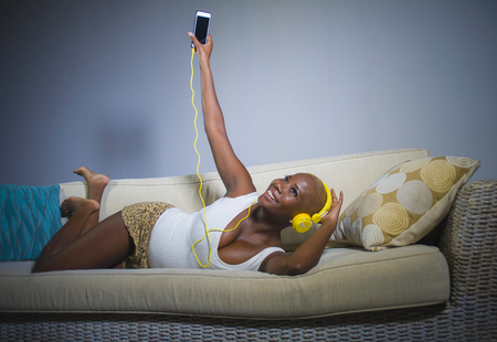 young happy and beautiful relaxed black afro American woman listening to music with headphones and mobile phone at home sofa couch smiling cheerful enjoying song lying comfortable and sweet