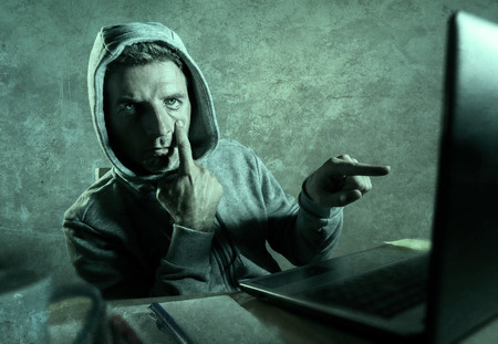 dangerous looking hacker man in hoodie hacking internet computer system pointing his eyes warning about his ability to break password stalking accounts in cyber security concept 스톡 콘텐츠