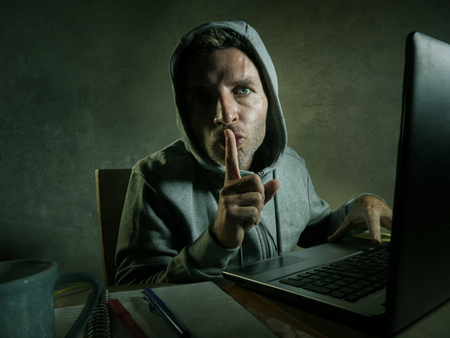 dangerous looking young hacker man in hoodie typing on laptop computer hacking and decoding system data or having illegal access breaking password on cyber attack and internet security concept